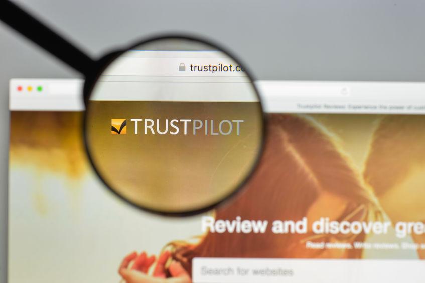 Home page del sito Trustpilot con logo in una lente di ingrandimento