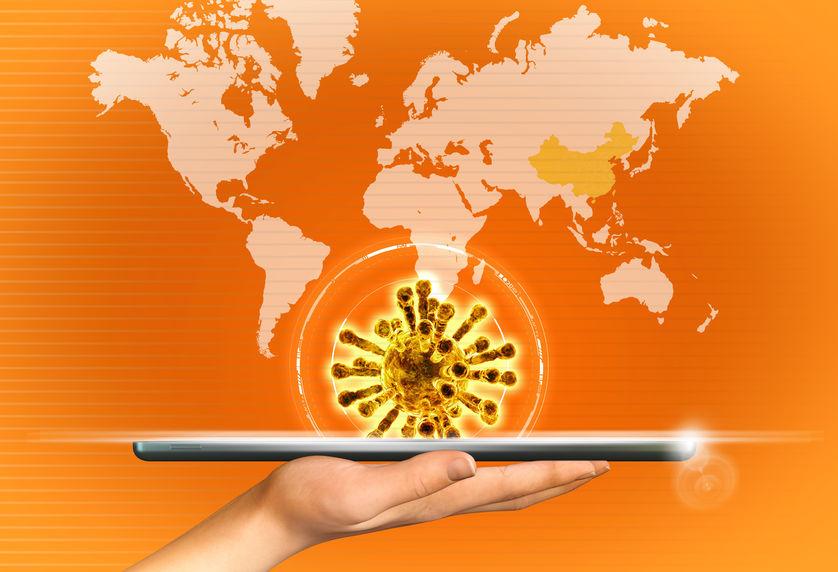 Il Coronavirus esce da un tablet sostenuto da una mano, sullo sfondo dei continenti
